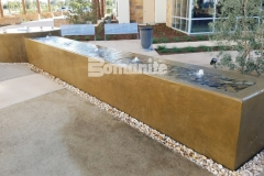 Bomanite integrally colored concrete was installed here with a smooth trowel finish to create a relaxing water feature that complements the tranquil and therapeutic design aesthetic in this outdoor space.