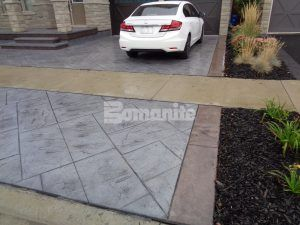 Angled view of driveway, porch, and steps showing Bomanite Imprint Systems decorative concrete using Yorkshire Stone Pattern with Bomanite Shale Gray Color Hardener installed at a residence in Burlington, Ontario, by Bomanite Toronto located in Vaughn, Ontario near Toronto Canada.