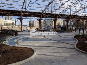 Iron Umbrella Train Shed designated as a National Historic Landmark houses a river of glass with Bomanite Revealed Exposed Aggregate for the River Confluence at the St. Louis Aquarium installed by Musselman & Hall Contractors.
