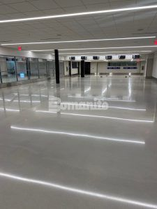 Long view of hallway lined with windows at the newly renovated Brownsville South Padre Island International Airport in Brownsville, TX, using Bomanite Custom Polishing Modena SL System decorative concrete flooring installed by Texas Bomanite.